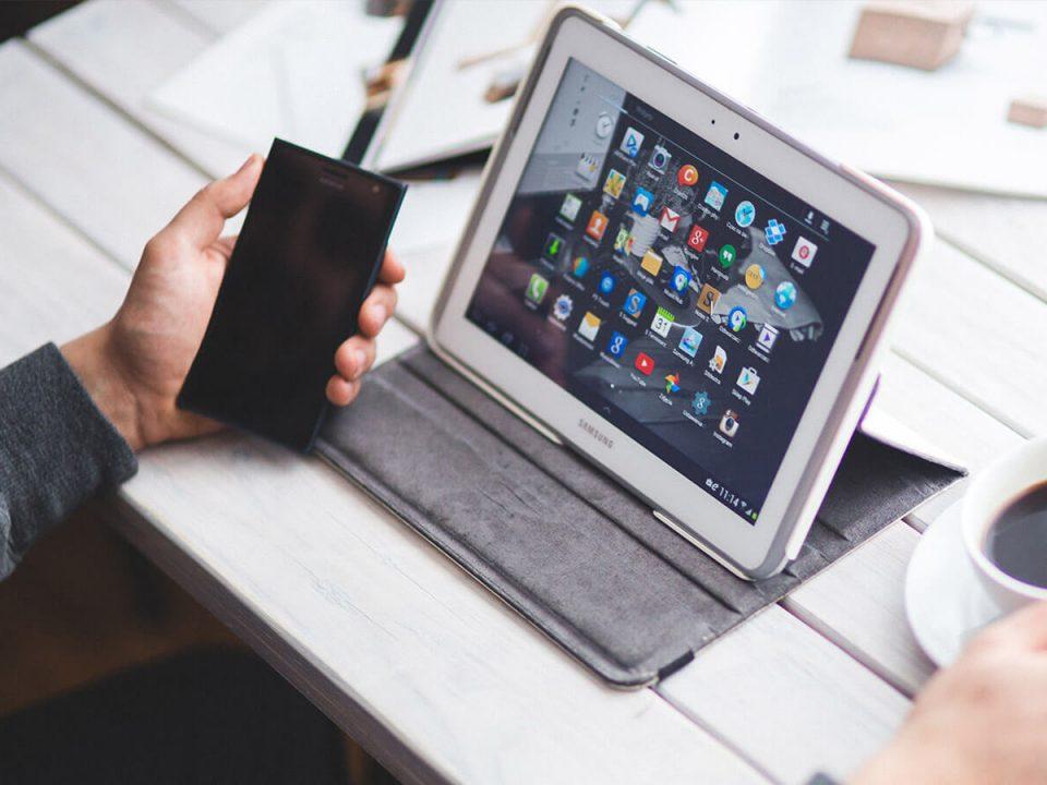 Homem com celular e tablet