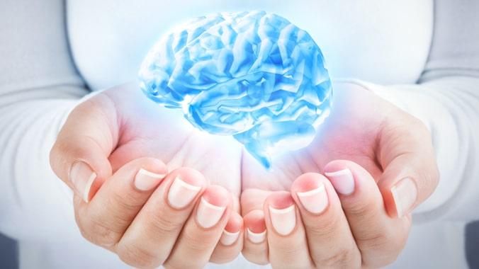 cérebro azul segurado por duas mãos